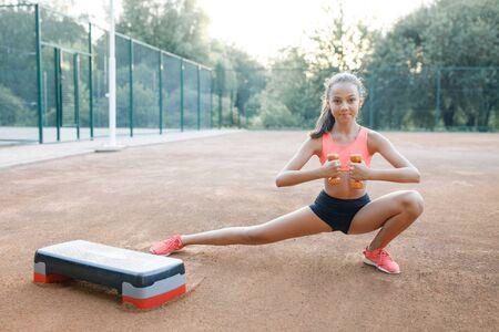 Une jolie et mignonne adolescente tient des haltères dans ses bras et effectue divers exercices en plein air. Mode de vie