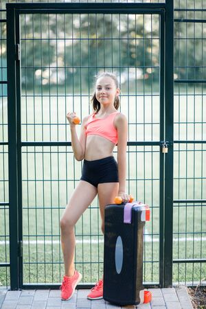 Young pretty girl of slender body building, dressed in sports form is engaged in outdoor sports. Funny summer holidays Stock fotó