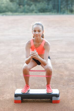 A young, pretty girl of slender body, dressed in a sports uniform, spends time on a sports ground and performs physical exercises. Lifestyle 写真素材