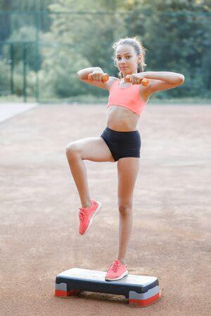 Ein süßes, hübsches Teenager-Mädchen hält Hanteln in den Armen und führt verschiedene Outdoor-Übungen durch. Lebensstil
