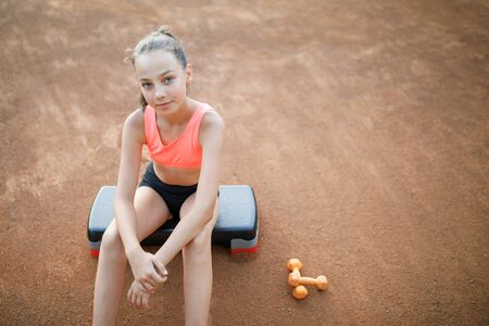 A cute, pretty teenage girl sits on a step platform and relaxes after her workout on outdoor. Lifestyle
