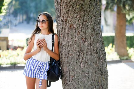 A cute, pretty teenage girl drinks a cool drink in the summer heat and has fun. 写真素材