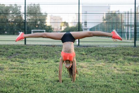 Una joven y simpática chica de musculación esbelta, vestida con una forma de deporte, realiza ejercicios gimnásticos al aire libre Foto de archivo