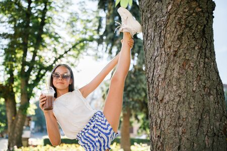 A cute, pretty teenage girl drinks a cool drink in the summer heat and has fun. Funny summer holidays