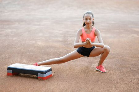 A cute, pretty teenage girl performs various outdoor exercises Stok Fotoğraf
