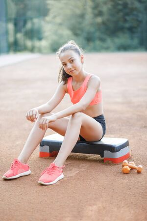 A cute, pretty teenage girl sits on a step platform and relaxes after her workout on outdoor Stockfoto