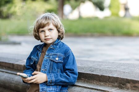 Cute blond guy, school year fun running time on the street and holds a smartphone in his hands Banco de Imagens