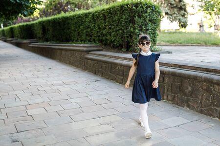 A cute schoolgirl girl is having fun on the street in the park. The girl is dressed in school uniform Banco de Imagens