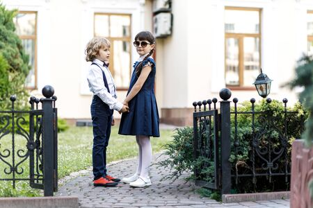 Cute blond guy and cute girl, school year fun time outdoors. 写真素材