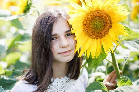 Pretty teen girl standing in a field near beautiful sunflower.