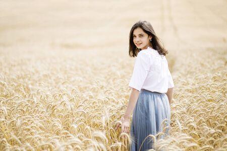 Beauty Girl Outdoors enjoying nature. Beautiful Teenage Model girl running on wheat field Reklamní fotografie