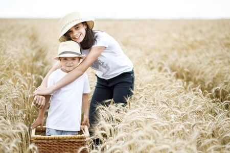 Happy brother and sister having fun on the field with wheat.