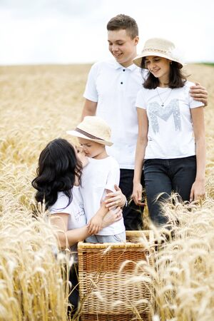 Happy family - brothers, sister and mom have fun on the wheat field. 写真素材