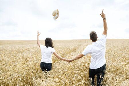 Beautiful happy couple - guy and girl having fun on the field among wheat ears, they run and have fun
