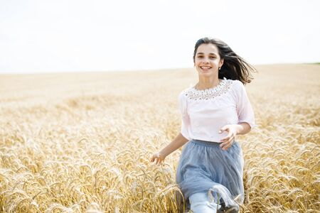 Beauty Girl Outdoors enjoying nature. Beautiful Teenage Model girl running on wheat field