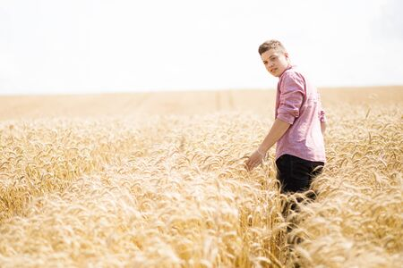 Courageous handsome guy standing in a field among wheat.