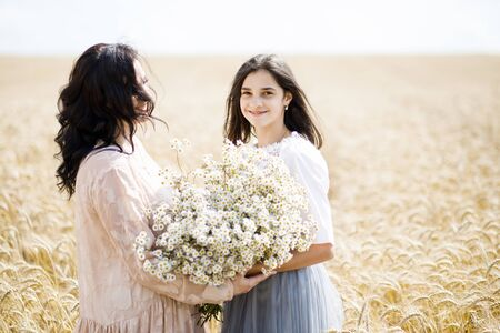 Happy family - mom and adult daughter have fun on the wheat field. The daughter gives her mother a big bouquet of flowers. Mothers Day.