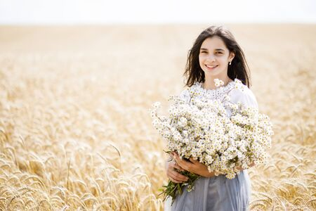 Pretty teen girl standing in a field among wheat. Girl holding a large bouquet of flowers