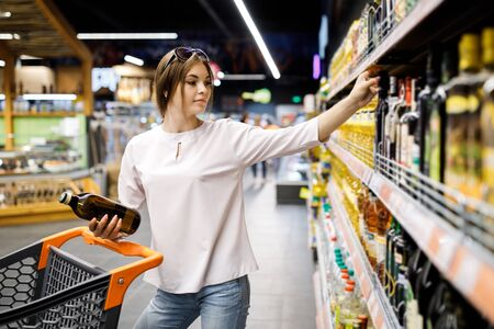 Young pretty girl is shopping in a big store. The girl buys groceries at the supermarket.