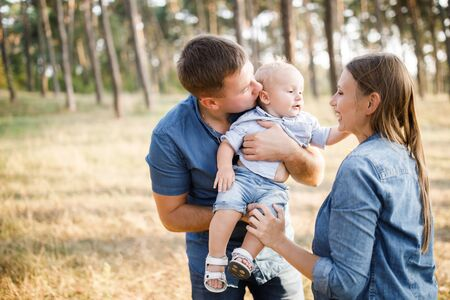 Beautiful happy family - parents and son, spend time in nature