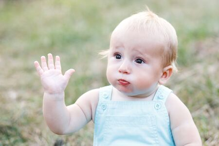 Cute blond boy sitting alone on the grass and waving his hand.