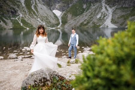 Cute young loving couple spending time in the mountains near the lake. A couple of newlyweds walk up alone Zdjęcie Seryjne