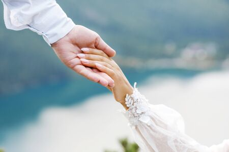 Young couple holding each others hands on a background of mountains. 写真素材