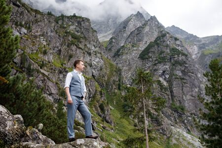 A young, sturdy man stands in the mountains near the lake. Magical landscape.