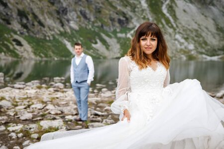 Cute young loving couple spending time in the mountains near the lake. A couple of newlyweds walk up alone 写真素材