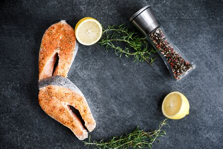 Fresh salmon steaks lie on a dark background, alongside lemon and rosemary and peppercorns with different types of peppers.