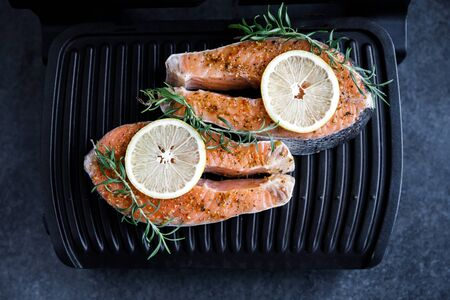 Preparation for frying a fresh salmon steak on an electric grill against a dark background, along with lemon and rosemary.