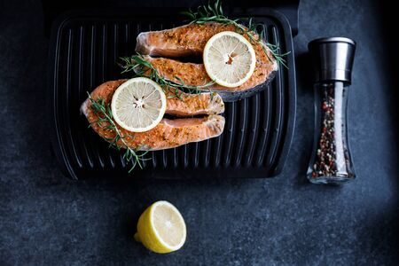 Preparation for frying a fresh salmon steak on an electric grill against a dark background, along with lemon and rosemary, a peppercorn with different types of peppers.