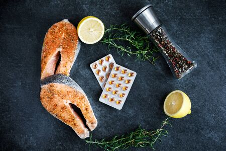 Fresh salmon steaks lie on a dark background, alongside lemon and rosemary, a peppercorn with various types of peppers and vitamins for daily consumption.