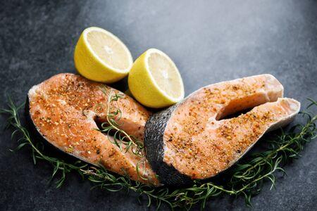 Fresh salmon steaks lie on a dark background, alongside lemon and rosemary.