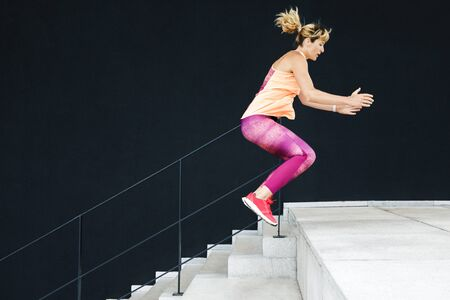 Young sports woman dressed in sportswear performs stitches on the steps outdoors. Healthy Lifestyle