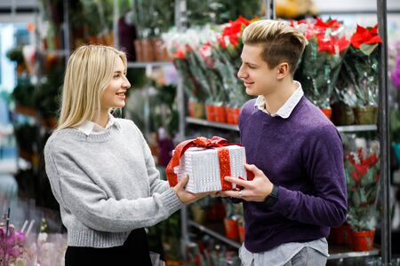 Portrait of young man with woman shopping presents in store in time before the winter holidays. Beautiful couple buys gifts for family and friends Banque d'images - 135503496