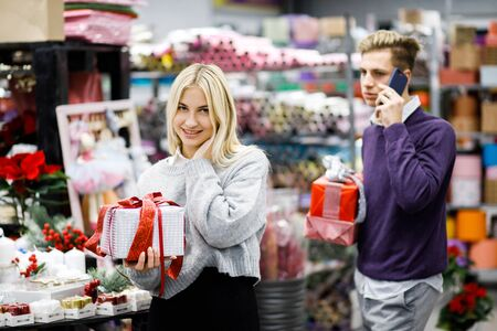 Portrait of young man with woman shopping presents in store in time before the winter holidays. Beautiful couple buys gifts for family and friends Reklamní fotografie - 135503411