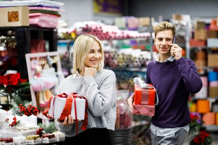 Portrait of young man with woman shopping presents in store in time before the winter holidays. Beautiful couple buys gifts for family and friends Banque d'images - 135503519