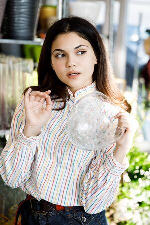 Hübsches junges brünettes Mädchen wählt eine Vase im Laden.