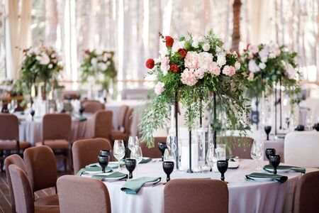 Festive wedding table setting with flowers, napkins, cutlery, glasses and candles, bright summer table decor.