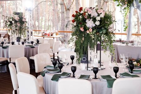 Festive wedding table setting with flowers, napkins, cutlery, glasses and candles, bright summer table decor. Foto de archivo