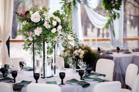 Festlicher Hochzeitstisch mit Blumen, Servietten, Besteck, Gläsern und Kerzen, helle Sommertischdekoration.