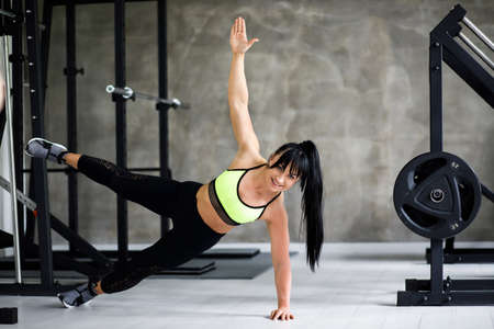 Portrait fitness training athletic sporty woman doing plank exercise in gym