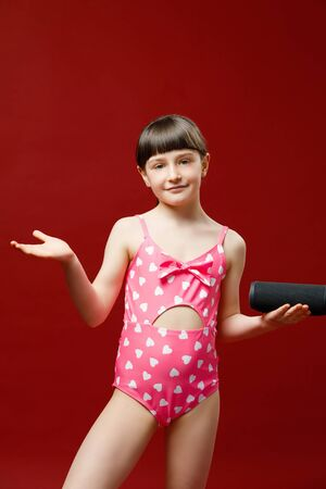 Isolated shot of charming little girl in swimsuit posing in studio with speaker for music.