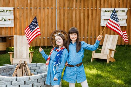 Two beautiful school-age girls spend time in the yard, holding USA flags