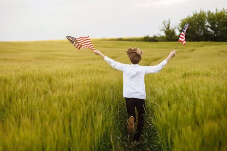 Boy runing with the american flag on the green wheat field celebrating national independence day