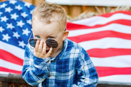 Cute blond boy in stylish glasses stands in the yard on the background of the American flag