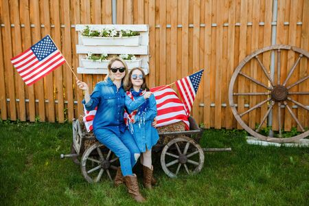 Mom and daughter have fun and celebrate on the background of the American flag. Independence Day Фото со стока