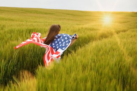 Carefree pretty girl running and smiling on the green field with a blowing flag of USA. Independence Day