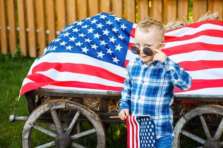 Cute blond boy in stylish glasses stands in the yard on the background of the American flag. Independence Day